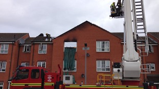 Fire crews work to stabilise the burnt-out building