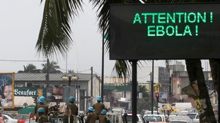 A U.N. convoy of soldiers passes a screen displaying a message on Ebola on a street in Abidjan.
