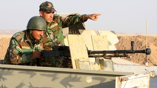 Kurdish Peshmerga troops train on a medium machine gun.