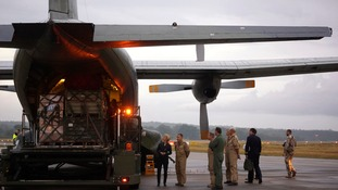 German Defence Minister Ursula von der Leyen (L) watches as humanitarian aid is loaded to an airforce Transall C-160 plane.