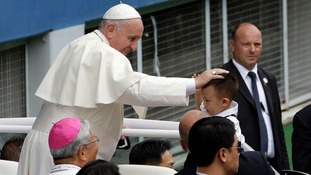Pope Francis blesses a child upon his arrival for the Holy Mass at Daejeon World Cup stadium in Daejeon.