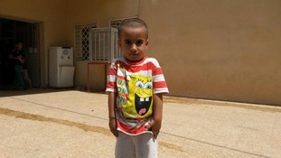 A young Yazidi boy named Rayan poses for a photo.