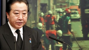 Japanese Prime Minister Yoshihiko Noda speaks in front of an image of disaster-hit areas