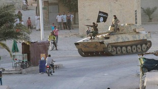 Islamic State militants with a captured armoured vehicle in July.
