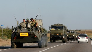 Russian servicemen ride atop an armoured personnel carrier (APC) as they escort a column of military vehicles.