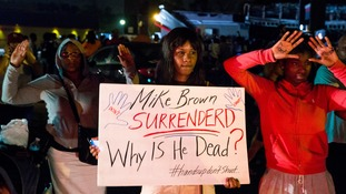 A protester holds a sign as others raise their hands during a demonstration against the shooting of Michael Brown by police.