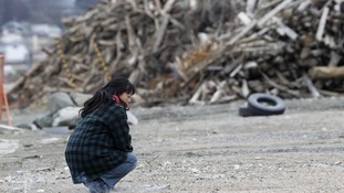 A woman kneels near a pile of debris while offering prayers in the devastated city of Rikuzentakata