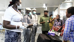Nigerian custom officers wearing face masks and gloves screen passengers arriving at Nnamdi Azikiwe International Airport