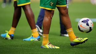 Norwich City player wearing rainbow laces on their football boots as part of an anti-homophobia campaign