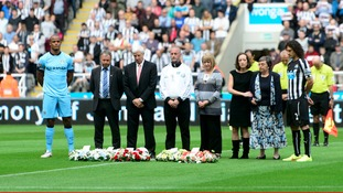 Families of Liam Sweeney and John Alder stand next to Fabricio Collocini and Vincent Kompany during the silence
