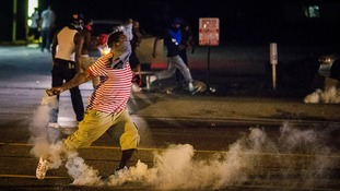 A protester picks up a gas canister to throw back towards the police