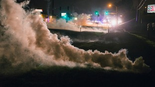 Tear gas rises from the ground after having been fired upon protesters