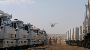 A military helicopter flies above a Russian convoy of trucks carrying humanitarian aid for Ukraine.