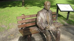 A statue of Alan Turing on a bench in Sackville Gardens, Manchester