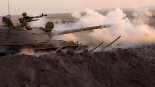 Kurdish Peshmerga fighters fire at Islamic Militants.