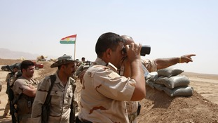 Kurdish Peshmerga fighters stand guard