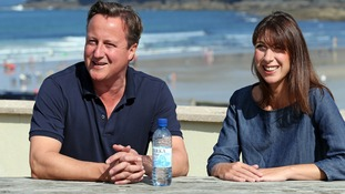 Britain's Prime Minister David Cameron and his wife Samantha pose for a photograph outside a cafe on summer holiday last year.