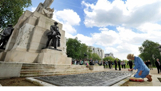 The Duchess of Cornwall kneels at the foot of the Royal Artillery Memorial on Hyde Park Corner.
