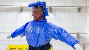 Ward physician Thomas Klotzkowski puts on his protective suit before going to work in the infections diseases ward at Charite hospital in Berlin