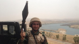 One Peshmerga soldier carries an RPG on top of the dam.