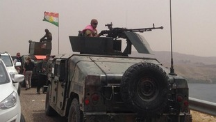 Two Peshmerga vehicles can be seen as a Kurdish flag flies over the dam.