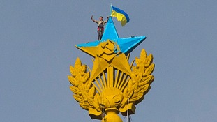 Photo purporting to show a man takes a 'selfie' as he holds a Ukrainian flag atop a building in Moscow
