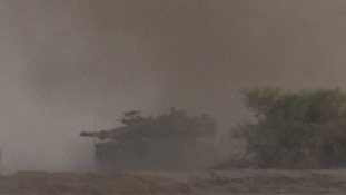 An Israeli tank kicks up dust near the Gaza border.