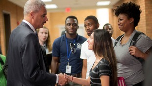 Attorney General Eric Holder shakes hands with Bri Ehsan, 25
