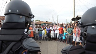 Liberia security forces dressed in riot gear control a crowd of people in the West Point area.