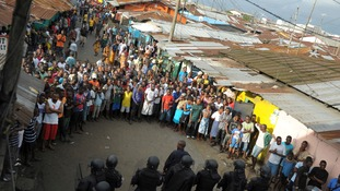 Liberian security forces stand in front of protesters after clashes at West Point neighbourhood in Monrovia.