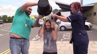 Comedian Russell Brand squeals as he gets a soaking from two NHS workers.
