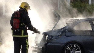 Firefighters soak what's left of the car
