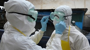 Medical workers in the vicinity of Ebola patients must wear head-to-foot protective clothing
