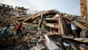 Palestinians collect their belongings from under the rubble