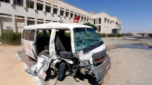 A damaged ambulance is parked in front of the National Hospital of al-Tabqa