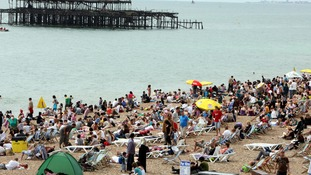 Thousands flock to Brighton, Sussex, as Britain basks in warm sunshine.