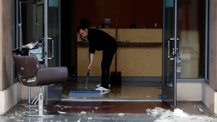 A man sweeps broken tiles and wreckage from his Napa shop.