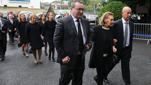 Flanked by her two sons Kathleen Reynolds attends the funeral of her late husband Albert.