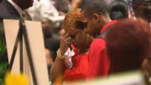 A guest comforts Michael Brown's mother