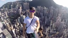 The world's most dangerous selfie? Daredevil strikes a pose on top of Hong Kong skyscraper.