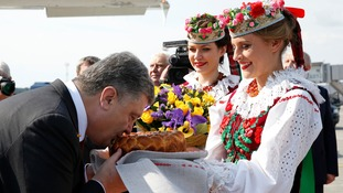 Ukraine's President Petro Poroshenko takes part in a traditional bread and salt ceremony upon his arrival at an airport outside Minsk.