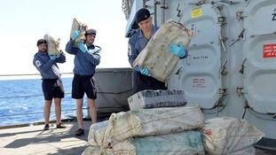 Crew of HMS Argyll carry bags of cocaine seized from a suspicious vessel in the Caribbean