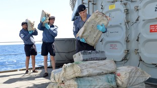 Sailors from HMS Argyll pile the seized drugs on board the warship.