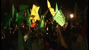 Residents wave flags on the streets of Gaza City.