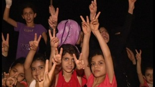 Children offer peace signs to cameras.