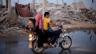 A family passes houses destroyed in shelling attacks en route to their home in Gaza