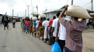 Relatives stand in line at a checkpoint outside the Ebola quarantine area of West Point in Monrovia, Liberia