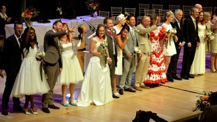 Couples celebrate their wedding on stage.