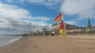 flag blowing in the wind and blue skies over Bridlington beach
