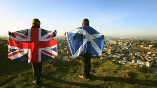 Two people hold a Union flag and a Scottish flag.